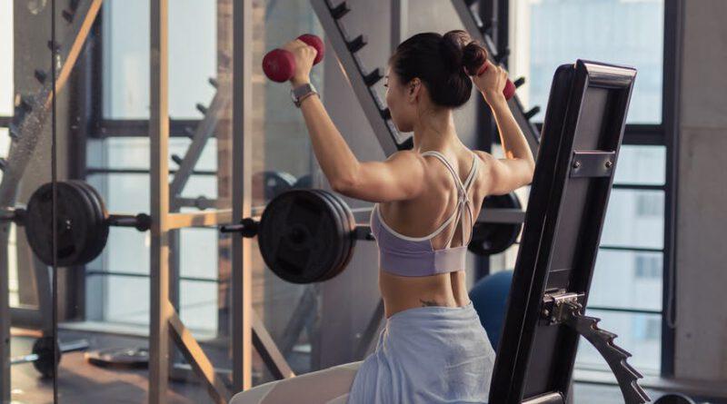 photo of woman raising dumbbells